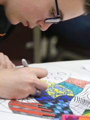 Mason Beam, a seventh grader at Lucas, works on a project during Artapalooza on Friday at the Mid-Ohio Educational Services Center.