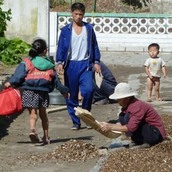Residents dry crops outside their homes in 2010 at a collective farm about 12 miles from the center of Pyongyang, North Korea.