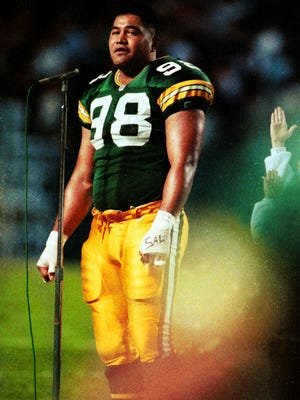 Green Bay Packers defensive tackle Esera Tuaolo sings the national anthem before the game against the Chicago Bears at Lambeau Field on Oct. 17, 1991.
