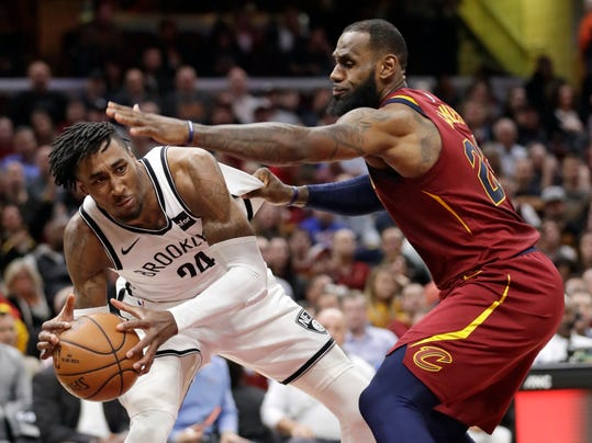 Brooklyn Nets' Rondae Hollis-Jefferson, left, looks to pass the ball as Cleveland Cavaliers' LeBron James defends during the first half of an NBA basketball game, Tuesday, Feb. 27, 2018, in Cleveland. (AP Photo/Tony Dejak)