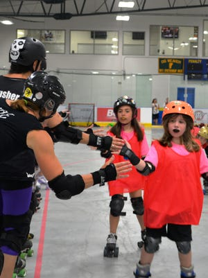 Girls slap hands at the Minor Catastrophes summer day camp hosted by Green Mountain Derby Dames at Essex Skating Center last week.