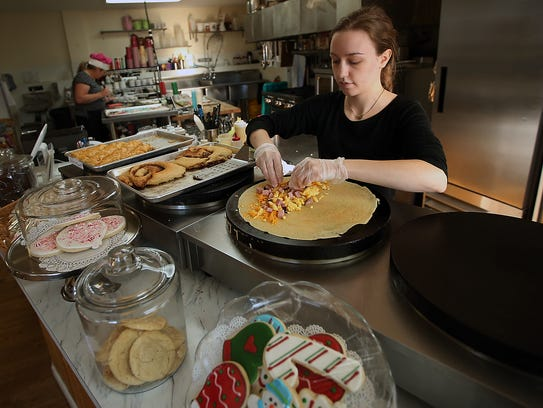 Claire Cline fills a crepe with eggs,cheese and ham at the Sugar Studio in Silverdale.