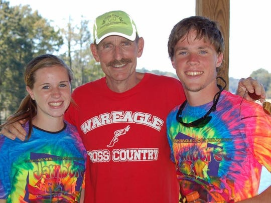 Wakulla cross country coach Paul Hoover with two of his former runners.