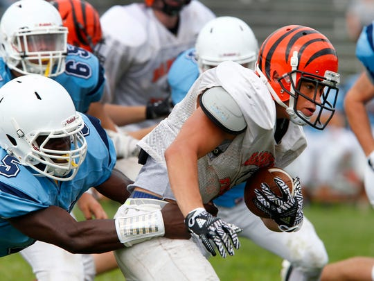 Barnegat's Charlie Cotton keeps running wrapped up by a Freehold Township defender during a scrimmage against Barnegat in Freehold Tuesday, August 22, 2017