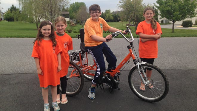 The Boileau sisters – Peyton (from left), Brooke and Taylor – join Preston Buenaga. Bikes like Preston's cost between $1,400 and $2,500, according to Deb Buenaga. She and her husband Steve founded Preston's March for Energy after Preston was given his bicycle.