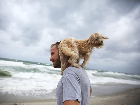 Ted Houston and his dog Kermit visit the beach as Hurricane