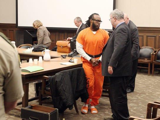 Justin Marshall walks past defense attorney Thomas