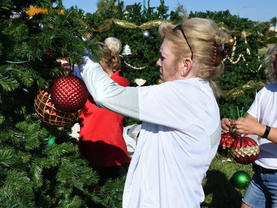 Gerry Richards hangs a an ornament on the tree. Workers