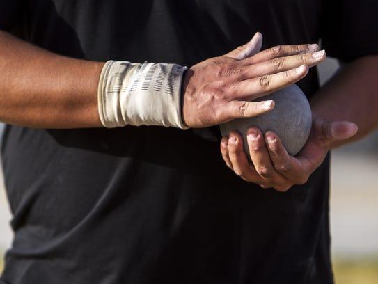 Desert Edge's Tyson Jones holds a shot put ball in