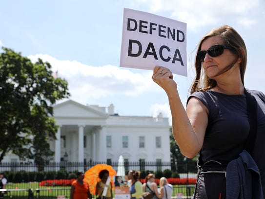 A woman demonstrates in favor of DACA in front of the White House.