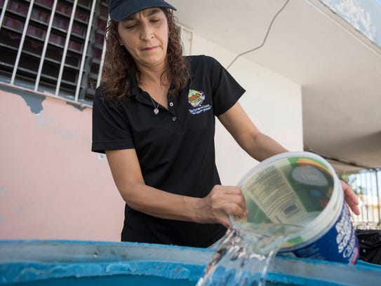 Michelle Rebollo transfers water from one barrel to