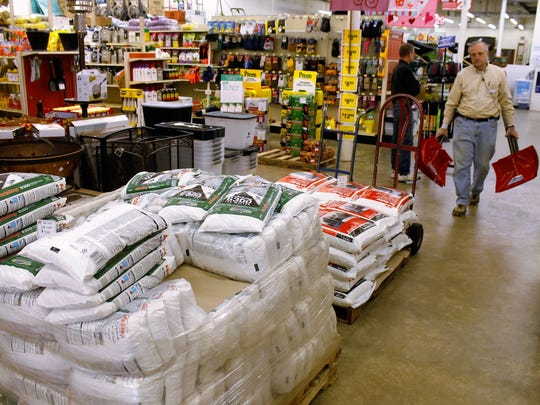 A worker of a hardware store walks past a pallet of