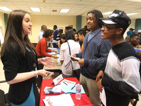 Michelle Paul, a recruiter with Unisys UTS explains employment opportunities to Jamarus Williams, 18, middle, and Demeatris White, 16, both of Rochester  during a job fair offered by RochesterWorks and the NYS Department of Labor.