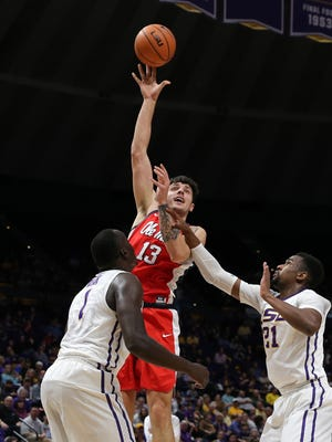 Feb 10, 2018; Baton Rouge, LA, USA; Mississippi Rebels center Dominik Olejniczak (13) shoots a jump shot in the first half against LSU Tigers forward Duop Reath (1) and forward Aaron Epps (21) at Pete Maravich Assembly Center. Mandatory Credit: Stephen Lew-USA TODAY Sports