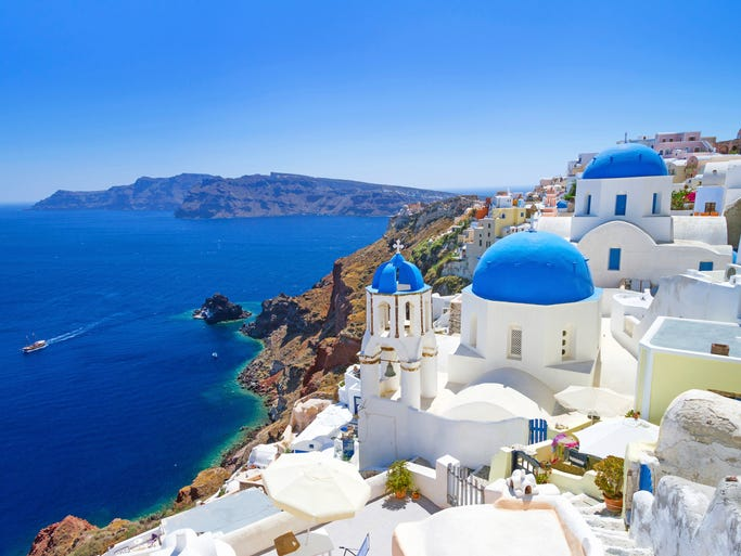 The Greek island of Santorini is dotted with                                                          white-washed,                                                          blue