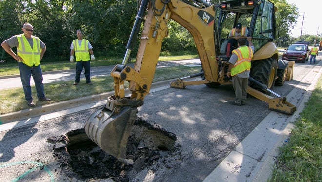 A sink hole on Rickett Rd. in Brighton is attended to by Brighton DPW staff Friday, June 29, 2018.