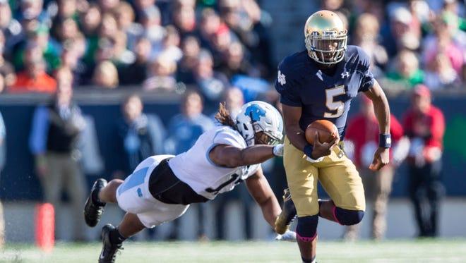 Notre Dame Fighting Irish quarterback Everett Golson (5) runs the ball as North Carolina Tar Heels defensive end Dajaun Drennon (17) defends in the first quarter at Notre Dame Stadium.