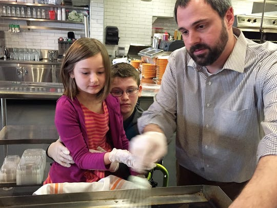 """Kate Woodruff sits on her brother Ethan Woodruff's lap while Dee Hust, general manager of Babalu demonstrates how to make a tortilla. The restaurant is hosting """"Ethan's Taco Shop"""" to raise funds for Ethan's ongoing physical therapy requirements."""