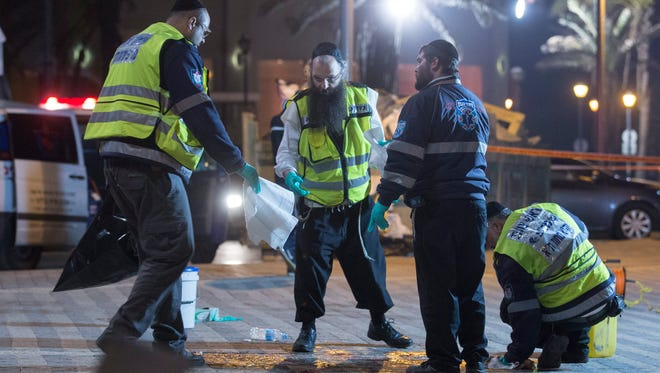 An ultra-Orthodox Jewish burial society cleans up blood and medical bandages at the scene a stabbing attack on a sea side walking area in old Jaffa, just south of Tel Aviv, on March 8 2016, after a Palestinian attacker went on a stabbing spree and wounded 10 people before he was shot and killed.