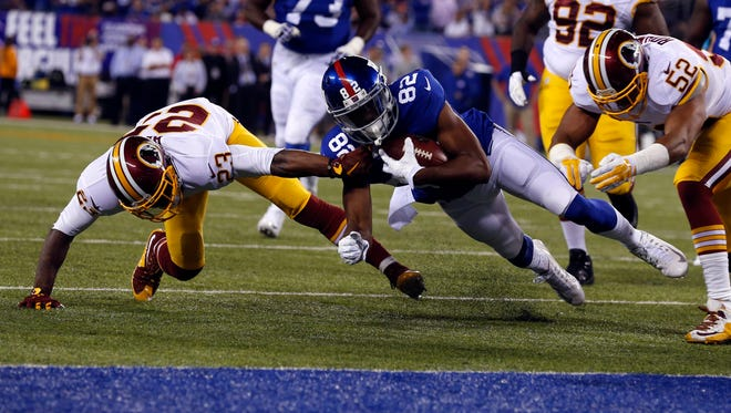 New York Giants wide receiver Rueben Randle (82) is brought down just outside the end zone by Washington Redskins cornerback DeAngelo Hall (23) during the first half at MetLife Stadium.