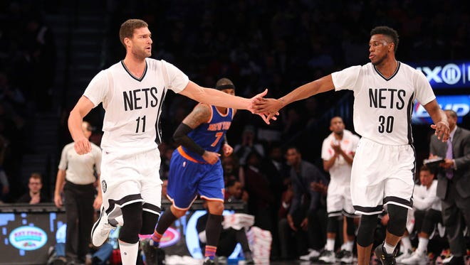 Feb 19, 2016: Brooklyn Nets center Brook Lopez (11) high fives Brooklyn Nets power forward Thaddeus Young (30) in front of New York Knicks small forward Carmelo Anthony (7) during the second quarter at Barclays Center. The Nets defeated the Knicks 109-98.