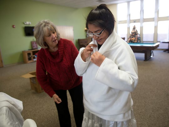 Kay Baker, left, helps Jennifer Benally with her angel costume at Navajo Ministries in Farmington.