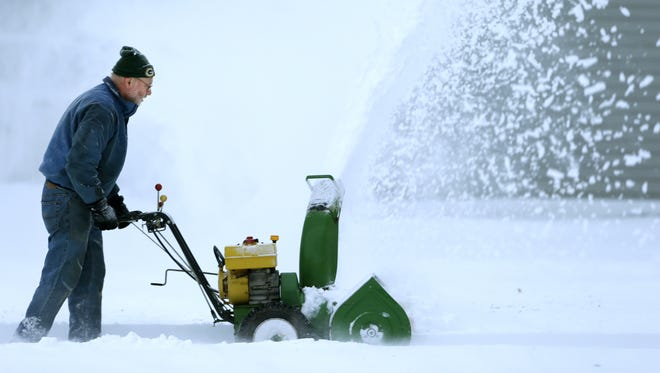 Dave Ebben of Grand Chute sends a stream of snow into the air Tuesday morning as he helps clear a neighbor's driveway with a snow blower after overnight storms swept through the Fox Cities.