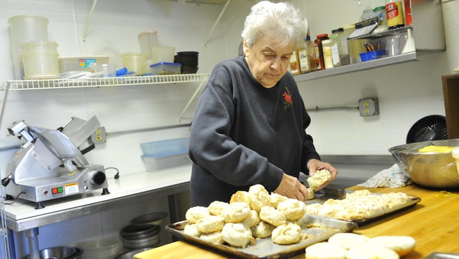 Lois Frank, owner of Grandma's USA Cafe, takes a few moments to help in the kitchen, working with homemade baking soda biscuits which will be used for biscuits and gravy.