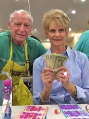 Bernie Seidman, member of the Bingo Committee, gives prize money to the big winner, Andrea Bradley of Naples.