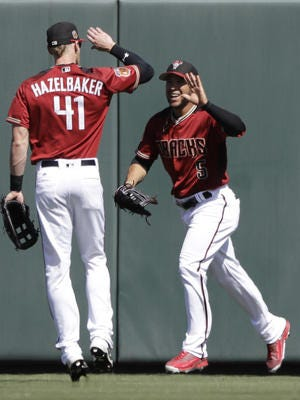 Diamondbacks outfielder Gregor Blanco is congratulated by Jeremy Hazelbaker after Blanco made a catch during a spring training game on March 7. Hazelbaker won one of the Diamondbacks' last roster spots and has reached safely in his first eight plate appearances this season.