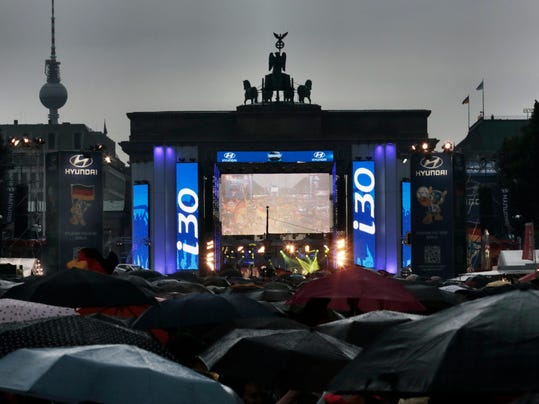 During heavy rain thousands of German soccer fans wait for the live broadcast of the final match  between Germany and Argentina of the soccer World Cup in Rio de Janeiro, Brazil,  at a public viewing area called 'Fan Mile' in front of the Brandenburg Gate in Berlin, Sunday, July 13, 2014. (AP Photo/Markus Schreiber)