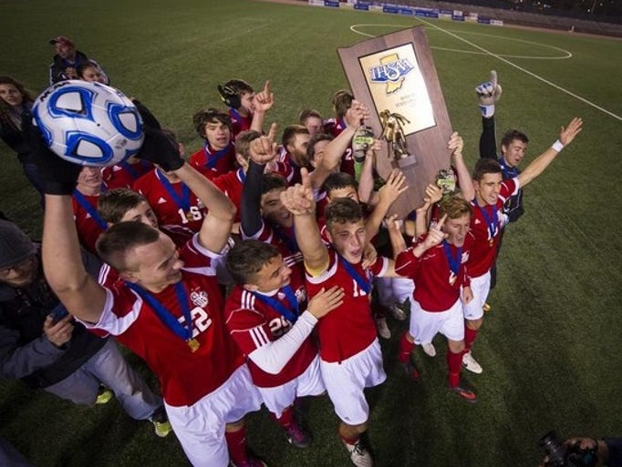 The Crown Point team celebrates their victory after the 20th Annual Boy's Soccer State Finals at Michael A. Carroll Soccer Stadium, Saturday, November 2, 2013. Crown Point defeated Avon 3-1 in overtime.