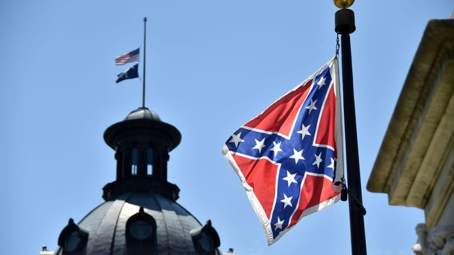The South Carolina and U.S. flags fly at half-staff atop the Capitol in Columbia. The Confederate flag flies on the statehouse grounds.