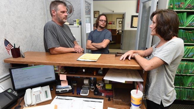 Danny Luncsford, left, and Todd Weaver, center, listen as Baxter County Clerk Canda Reese explains Friday the same-sex couple would have to wait to obtain a marriage license until further guidance from the state. The couple later received their marriage license Friday afternoon.