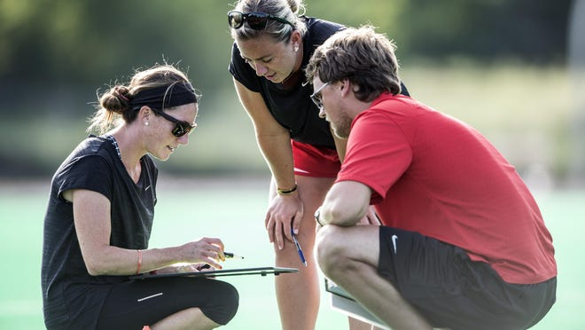 Rutgers field hockey coach Meredith Long, left, discusses strategy with assistant coaches Lauren Burke (center) and Roland Peekel.