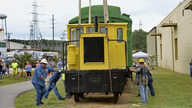 Workers secure a 1942 refurbished locomotive in a pocket park along the Swamp Rabbit Trail in Berea on Friday after the engine was lowered into place by a crane.