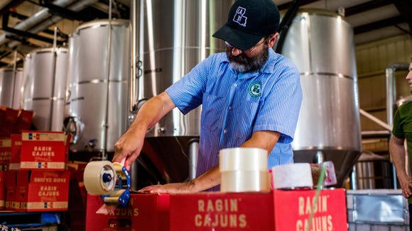 Karlos Knott, president of Bayou Teche Brewing in Arnaudville, seals a case of Ragin' Cajuns beer. The beer was created in partnership with the University of Louisiana at Lafayette and has become the brewery's best-seller.