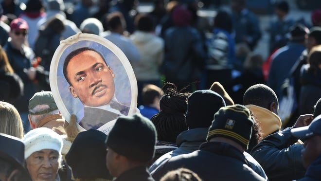 Attendees hold a portrait of Dr. Martin Luther King Jr. during the King Day at the Dome event on Monday in Columbia, S.C.