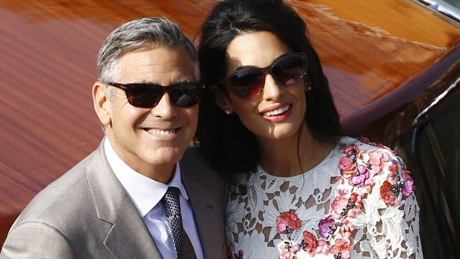 "US actor George Clooney and his wife Amal Alamuddin stand on a taxi boat on the Grand Canal on September 28, 2014 in Venice. Hollywood heartthrob George Clooney and Lebanese-British lawyer Amal Alamuddin married in Venice on Saturday September 27, 2014 before partying the night away with their A-list friends in one of the most high-profile celebrity weddings in years. ""George Clooney and Amal Alamuddin were married today (September 27) in a private ceremony in Venice, Italy,"" Clooney spokesman Stan Rosenfield said. The announcement came as a surprise as the pair were not expected to officially tie the knot until Monday, though they are still tipped for a civil ceremony at the town hall to officialise the marriage under Italian law.  AFP PHOTO / PIERRE TEYSSOTPIERRE TEYSSOT/AFP/Getty Images ORIG FILE ID: 533868706"