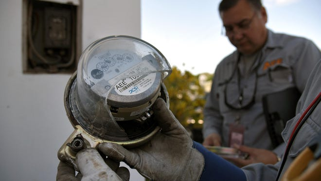 A worker from the Energy Theft Control Unit with Puerto Rico's Electric Power Authority holds an electric meter with broken glass during an inspection in Carolina, Puerto Rico.