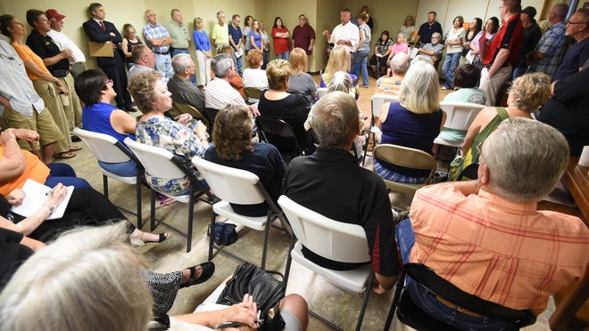 Cotter residents listen to Twin Lakes Recovery officials during a meeting held to inform the public about a reentry housing unit to serve state inmates that was opened briefly in the town. The facility's owners are now suing the city for revoking the business' occupancy permit.