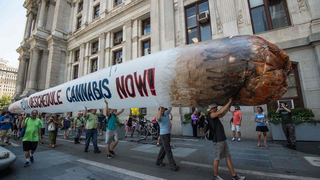 Supporters of Bernie Sanders hold a giant inflatable joint as part of a call to legalize marijuana during a rally Monday at City Hall in Philadelphia.