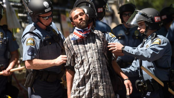 Joshua Lawrence is arrested by St. Paul police after protesters refused to move from in front of the Governor's residence on Summit Ave. in St. Paul, Minn. on Tuesday, July 26, 2016. Police have arrested an unknown number of protesters in front of the governor's mansion on St. Paul's Summit Avenue. Demonstrators have been camping outside the governor's residence since early July 7, a day after the shooting of Philando Castile, who was killed by a St. Anthony police officer during a traffic stop. (Scott Takushi/Pioneer Press via AP)