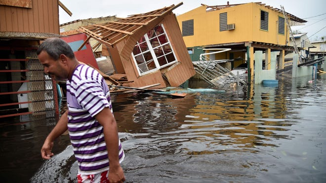 A man walks past destroyed homes in Catano, Puerto Rico, on Sept. 21, 2017, after Hurricane Maria. The storm is believed to be responsible for the deaths of 3,000 people.