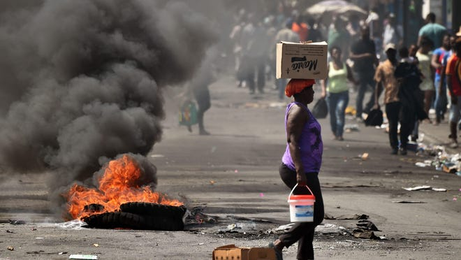 A tire placed by a small group of demonstrators burns on a street in the commune of Petion Ville in the Haitan capital Port-au-Prince, on Feb. 17, 2019.