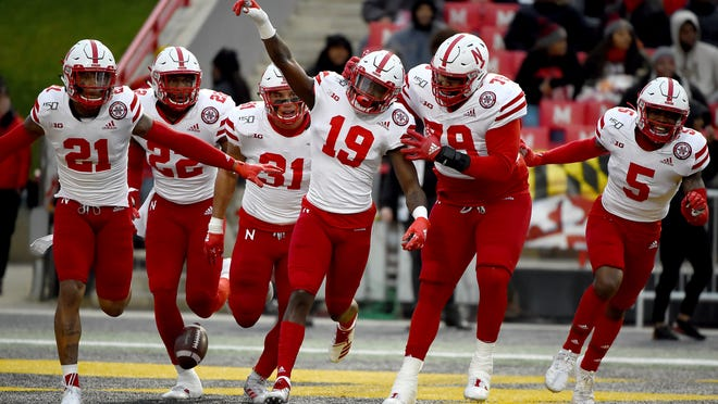 FILE - In this Saturday, Nov. 23, 2019, file photo, Nebraska safety Marquel Dismuke (19) celebrates with teammates after recovering a fumble from Maryland running back Javon Leake (20) during the first half of an NCAA college football game against Maryland, in College Park, Md. Nebraska's 24-sport program has about 600 athletes and is one of a handful that makes money. Though a 10% budget cut was announced recently, the program is able to absorb the cost of coronavirus testing, in part because of its affiliation with the university's medical school.