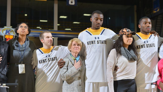 Kent State basketball players (from left) Jon Fleming, Jimmy Hall and Deon Edwin were joined on the court by fans and administrators, including former KSU President Beverly J. Warren (left of Hall), to promote racial solidarity during the team's home opener in November of 2016 at the M.A.C. Center.