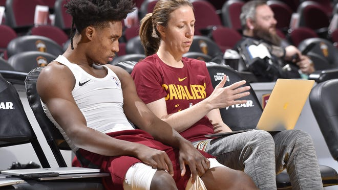 Lindsay Gottlieb and Collin Sexton of the avaliers watch film on the bench before a game in December.
