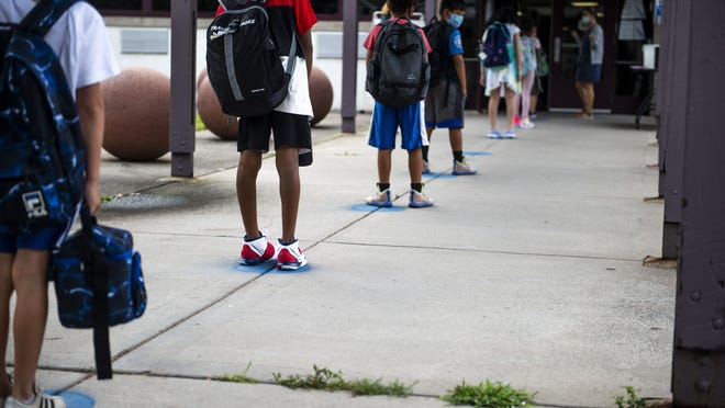 Young students wait socially distanced on blue dots as they wait to enter during the first day back to school at Lawrence Elementary School in Middletown.