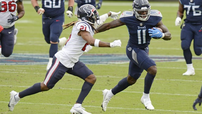 Tennessee Titans wide receiver A.J. Brown is chased by Houston Texans cornerback Bradley Roby during the Titans' 42-36 overtime win Sunday in Nashville, Tenn.